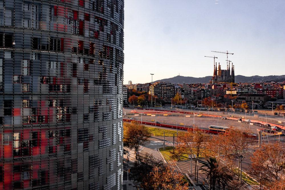 La Sagrada Familia con la Torre Glòries en primer plano, Barcelona, España.